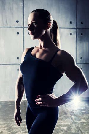 looking aside: Strong woman bodybuilder portrait looking aside. Contrast colors.