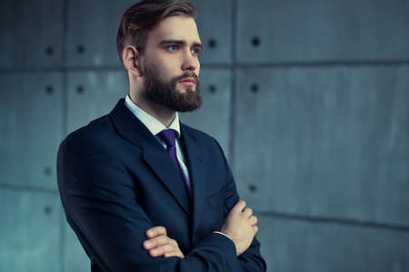 looking aside: Young handsome man with beard in black suit looking aside.
