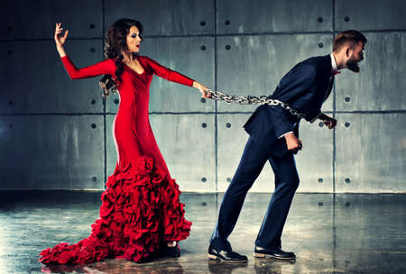 escape: Young woman in red dress holding man on heavy chain. He tries to escape. Elegant evening clothing. Stock Photo