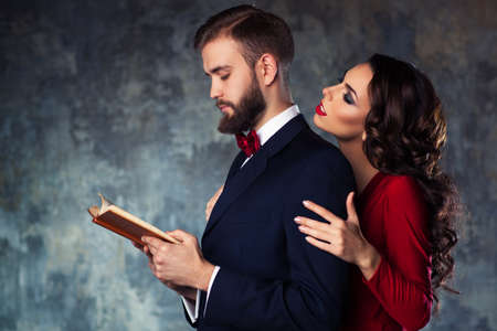 Young elegant couple in evening dress portrait. Man reading book and woman trying to attract and embrace him. 스톡 콘텐츠