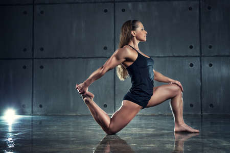 stretch: Strong woman bodybuilder stretching on wall background. Stock Photo