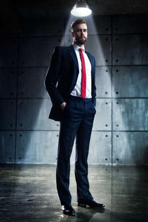 terno: Apuesto hombre de negocios joven con barba en traje negro de pie bajo la luz brillante en el interior urbano.