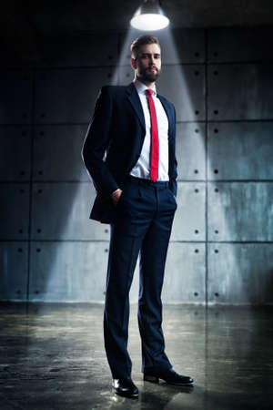 Young handsome businessman with beard in black suit standing under bright light in urban interior.