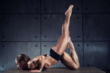 woman stretching: Strong woman bodybuilder stretching on wall background. Stock Photo