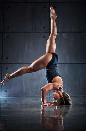 Strong woman bodybuilder standing upside down on wall background.