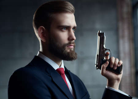 looking aside: Danger man with gun looking aside portrait. Stock Photo
