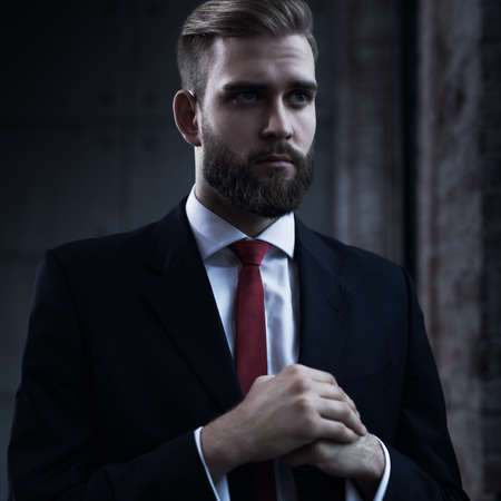 surly: Young serious businessman with beard in black suit portrait. Stock Photo