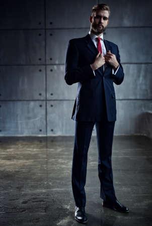 beau jeune homme: Beau jeune homme d'affaires avec la barbe en costume noir debout sur le mur arrière-plan.