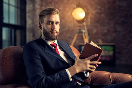 Young handsome businessman with beard in black suit sitting on chair reading book.