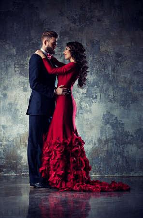 pareja abrazada: Elegante joven pareja de enamorados en traje de noche retrato. Mujer en rojo y el hombre en traje negro abrazo. Foto de archivo
