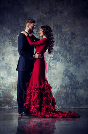 Young elegant loving couple in evening dress portrait. Woman in red and man in black suit embracing.