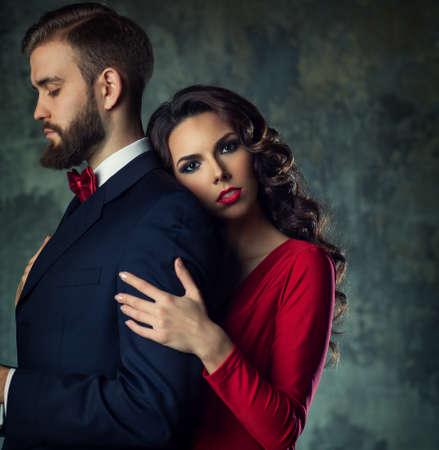 anochecer: Hombre elegante joven mujer abrazando. Él es serio y mirando a un lado. Concepto de Pelea. Foto de archivo
