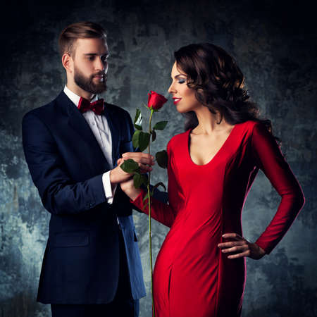sniff: Young elegant couple in evening dress portrait. Woman in red sniff rose. Focus on woman.