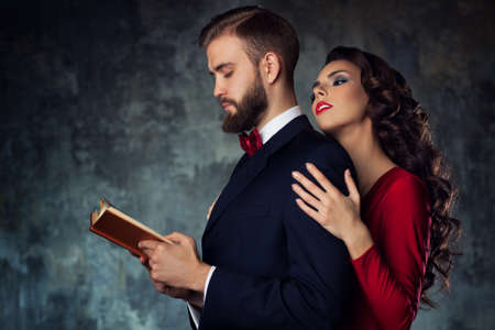 flirtation: Young elegant woman embracing man that reading book.