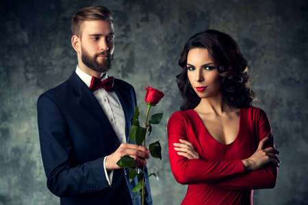 men and women: Young elegant couple in evening dress portrait. Man gives rose to woman. Focus on woman. Stock Photo
