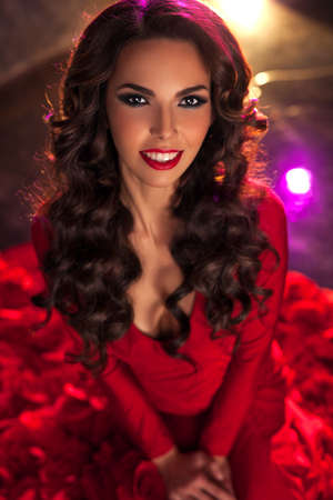 Young sexy brunette woman fashion portrait in red dress. photo