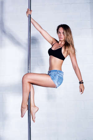 Young slim sexy pole dance woman in jeans shorts. Bright white interior.
