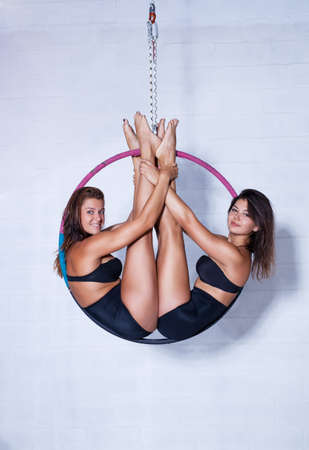 Two young slim sports women on ring in bright white interior photo