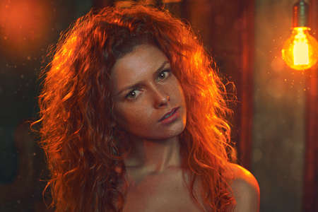 colores calidos: Mujer joven con el pelo rojo en el interior retrato. caliente de la lámpara efecto brillante. estilo de película de colores suaves.