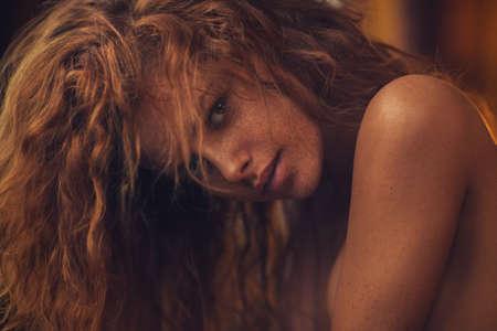 colores calidos: Mujer joven con el pelo rojo en el interior retrato. colores suaves y cálidos al estilo de película.