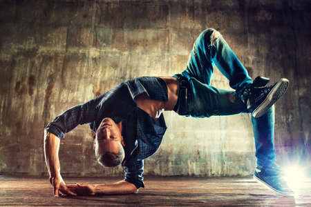 break: Young man break dancing on old wall background Stock Photo