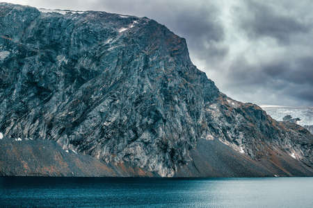 severe: Norway high mountains cold and severe landscape. Big mountain over lake.