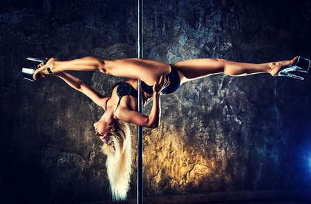Young blond sexy pole dance woman on old wall background. Contrast colors effect. Stock Photo