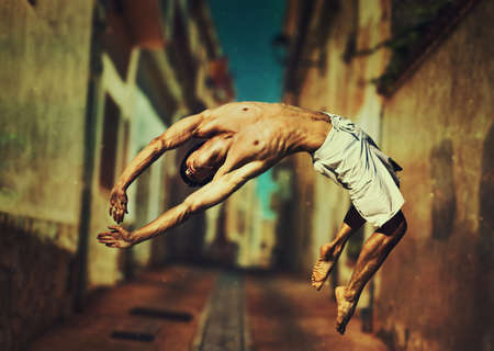 Young man dancer jumping on old town street background