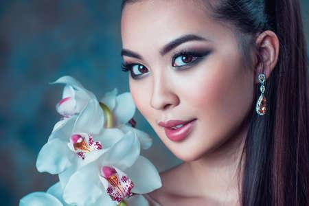 femme romantique: Jeune femme asiatique avec orchidée, fleur portrait