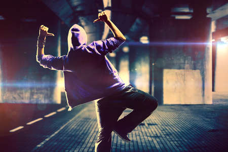 Young woman hip-hop dancer on urban background with flare effects