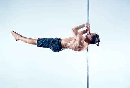 pole dancing: Young strong pole dancing man on blue and white background