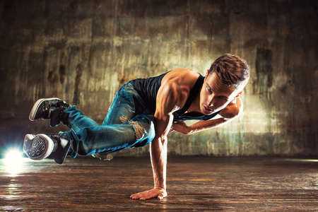 break dancer: Young man break dancing on old wall background Stock Photo