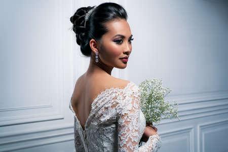 femme romantique: Jeune femme asiatique en robe blanche avec des fleurs portrait de la mode