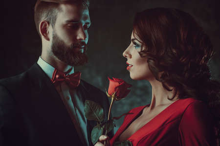 Young elegant couple. Woman in red holding rose and looking on man. Focus on woman. Vintage film style colors. photo