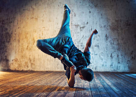 Young man break dancing on wall background. Blue and red lights effect.