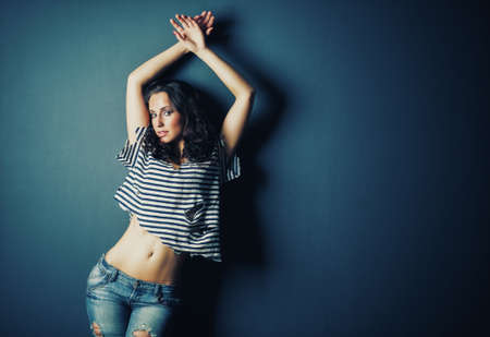 Young sexy woman in jeans posing on wall background. Soft blue tint. photo