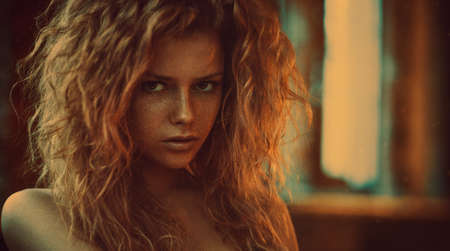 colores calidos: Mujer joven con el pelo rojo en el interior retrato. colores suaves y cálidos al estilo de película de época. Foto de archivo