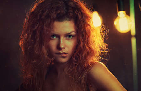 flirt: Young woman with red hair indoors portrait. Doubt and flirt emotion on face. Stock Photo