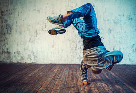 Young man break dancing on wall background. Vibrant colors effect. 스톡 콘텐츠