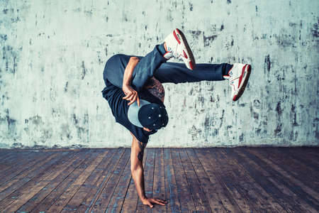 Young man break dancing on wall background Stockfoto