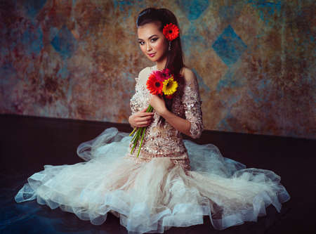Young asian woman in dress with flowers sitting on floor fashion portrait photo