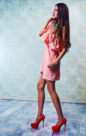 woman young: Young slim sexy fashion woman in long pink dress standing on wall background