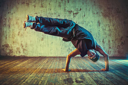 break: Young man break dancing on wall background. Blue and yellow vibrant colors tint.