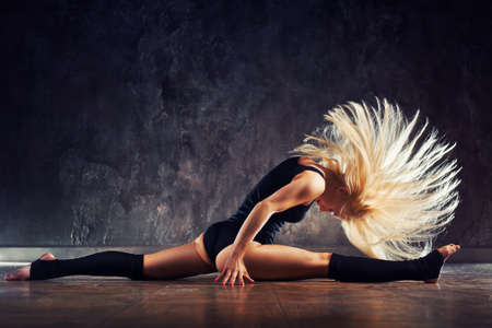 Young sports blond woman stretching legs and shaking hair on dark wall background
