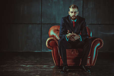 man in chair: Young handsome businessman with beard in black suit sitting on chair and talking with speaker. Film style retro colors effect.