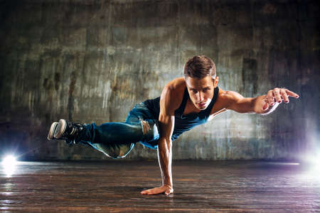 Young man break dancing and standing on one hand on old wall background