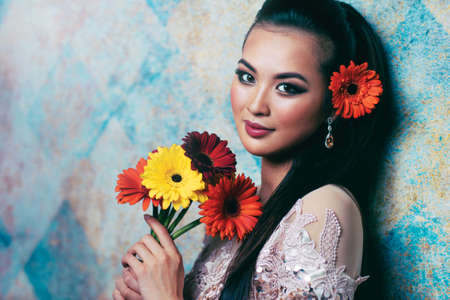 Young asian woman with flowers romantic portrait in bright white colors photo