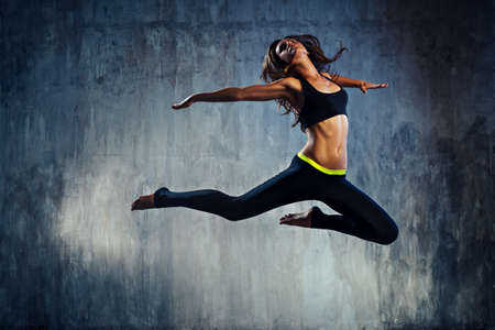 Young slim sports woman in black clothing jumping on old wall background