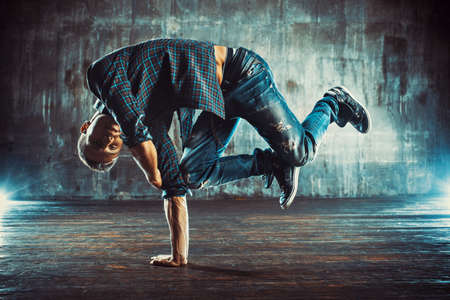 Young man in shirt and jeans break dancing on old wall background Stock Photo