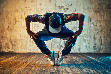 hip hop man: Young man break dancing on wall background. Blue and yellow colors tint. Tattoo on body.